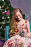 Muchacha hermosa que se sienta delante de un árbol de navidad Imágenes de archivo libres de regalías