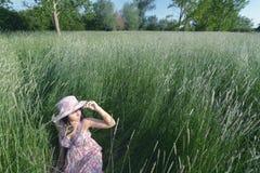 Muchacha hermosa que se sienta en alta hierba en prado de la primavera el día soleado Fotos de archivo