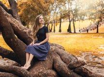 Muchacha hermosa que se sienta en el árbol en el paisaje del otoño Fotografía de archivo