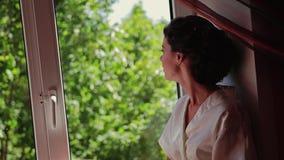 Muchacha hermosa hermosa que se sienta en el alféizar y que mira cuidadosamente el paisaje fuera de la ventana Un muy hermoso almacen de metraje de vídeo