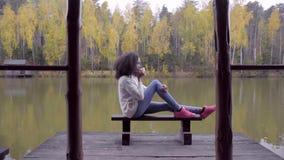 Muchacha hermosa que se sienta en el banco y el té caliente de consumición en el lago metrajes