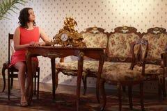 Muchacha hermosa que se sienta en el escritorio viejo Foto de archivo