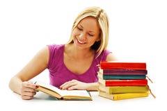 Muchacha hermosa que se sienta en el escritorio y el libro de lectura Imagen de archivo libre de regalías