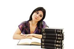 Muchacha hermosa que se sienta en el escritorio y el libro de lectura Foto de archivo