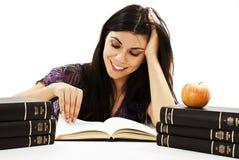 Muchacha hermosa que se sienta en el escritorio y el libro de lectura Foto de archivo libre de regalías