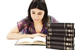 Muchacha hermosa que se sienta en el escritorio y el libro de lectura Imágenes de archivo libres de regalías