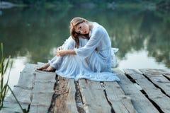 Muchacha hermosa que se sienta en el muelle agujereado Imagen de archivo libre de regalías