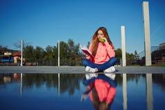 Muchacha hermosa que se sienta en el parque que lee un libro y que come la manzana Foto de archivo