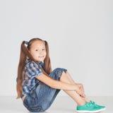 Muchacha hermosa que se sienta en el piso Fotos de archivo