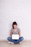 Muchacha hermosa que se sienta en el piso con el ordenador portátil y el espacio sobre w Fotografía de archivo libre de regalías