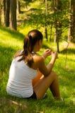 Muchacha hermosa que se sienta en hierba en el bosque Foto de archivo