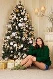 Muchacha hermosa que se sienta en la alfombra cerca del árbol de navidad Imagen de archivo libre de regalías