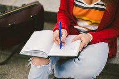 Muchacha hermosa que se sienta en la calle con un cuaderno y una pluma a disposición, haciendo notas y restos Foto de archivo libre de regalías