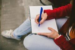 Muchacha hermosa que se sienta en la calle con un cuaderno y una pluma a disposición, haciendo notas y restos Fotografía de archivo libre de regalías