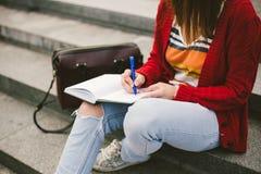 Muchacha hermosa que se sienta en la calle con un cuaderno y una pluma a disposición, haciendo notas y restos Fotos de archivo libres de regalías