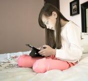 Muchacha hermosa que se sienta en la cama y que juega al juego de ordenador Imagenes de archivo