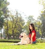 Muchacha hermosa que se sienta en la hierba con su perro Fotos de archivo