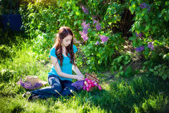 Muchacha hermosa que se sienta en la hierba con un ramo de lila en parque de la primavera Fotografía de archivo libre de regalías