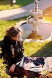 Muchacha hermosa que se sienta en la hierba en el parque Imágenes de archivo libres de regalías