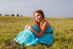 Muchacha hermosa que se sienta en la hierba verde, verano Imagen de archivo