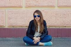 Muchacha hermosa que se sienta en la pared cercana de tierra Fotografía de archivo libre de regalías