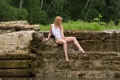 Muchacha hermosa que se sienta en la presa. Imagen de archivo