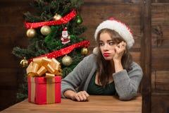 Muchacha hermosa que se sienta en la tabla con un actual árbol cercano del Año Nuevo Imágenes de archivo libres de regalías
