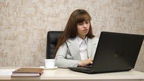 Muchacha hermosa que se sienta en silla en oficina y que mecanografía en el ordenador portátil y el café de consumición de la taz almacen de video