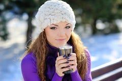 Muchacha hermosa que se sienta en un banco con una taza de café Imágenes de archivo libres de regalías