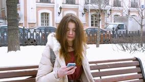 Muchacha hermosa que se sienta en un banco en invierno, esperando a su amigo, hablando en el teléfono almacen de video