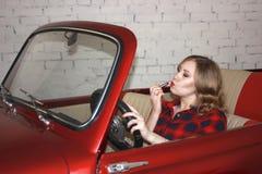 Muchacha hermosa que se sienta en un coche rojo y pinturas sus labios fotografía de archivo libre de regalías