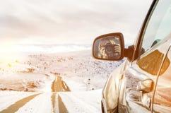 Muchacha hermosa que se sienta en un montar a caballo de SUV en las montañas foto de archivo