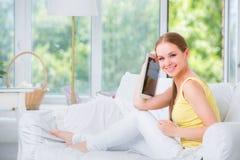 Muchacha hermosa que se sienta en un sofá contra la ventana y las demostraciones la tableta electrónica Fotografía de archivo libre de regalías