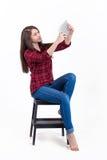 Muchacha hermosa que se sienta en una escalera de mano en el estudio y las miradas a Imagen de archivo libre de regalías
