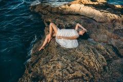 Muchacha hermosa que se sienta en una roca en el mar de la playa Fotos de archivo libres de regalías