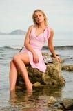 Muchacha hermosa que se sienta en una roca en la playa Foto de archivo