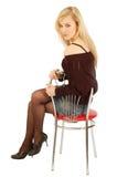Muchacha hermosa que se sienta en una silla imagenes de archivo