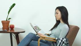 Muchacha hermosa que se sienta en una silla cómoda en casa y que lee una revista brillante almacen de metraje de vídeo