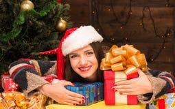 Muchacha hermosa que se sienta entre muchos presentes y regalos del Año Nuevo Fotografía de archivo