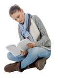 Muchacha hermosa que se sienta a piernas cruzadas, leyendo un libro en un blanco Imagen de archivo