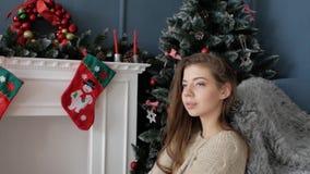 Muchacha hermosa que se sienta por la chimenea Año Nuevo metrajes