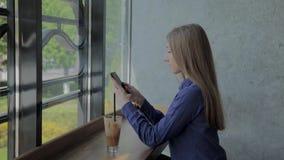 Muchacha hermosa que se sienta por la ventana con un tel?fono y una bebida en la tabla metrajes