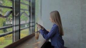 Muchacha hermosa que se sienta por la ventana con un tel?fono y una bebida en la tabla almacen de metraje de vídeo