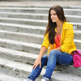 Muchacha hermosa que sienta en las escaleras en ropa colorida Fotografía de archivo libre de regalías