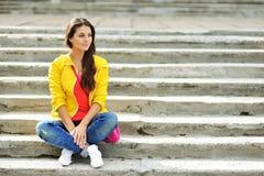 Muchacha hermosa que sienta en las escaleras en ropa colorida Fotos de archivo