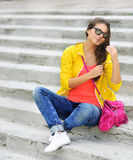 Muchacha hermosa que sienta en las escaleras en ropa colorida Imágenes de archivo libres de regalías