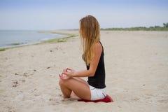 Muchacha hermosa que sienta y que mira el mar Yoga y hacer frente al amanecer Fotografía de archivo