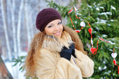Muchacha hermosa que sonríe en invierno en una capa de visión en el parque Foto de archivo libre de regalías