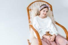 Muchacha hermosa que sonríe en la cámara mientras que sostiene el conejo y siéntase en mecedora Foto de archivo