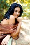 Muchacha hermosa que sonríe en parque con el vestido de la moda Fotos de archivo